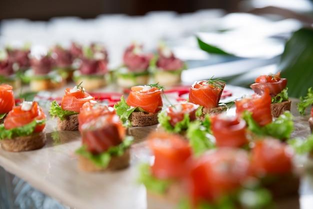 Mini kanapki z wędzonym łososiem na stole w formie bufetu