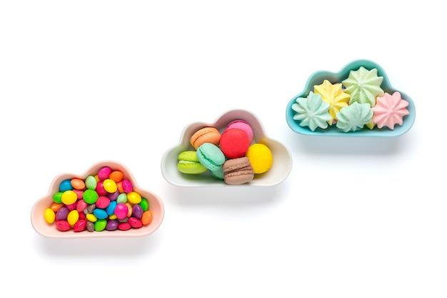 Mini kolorowe cukierki w misce w kształcie chmury na białym tle