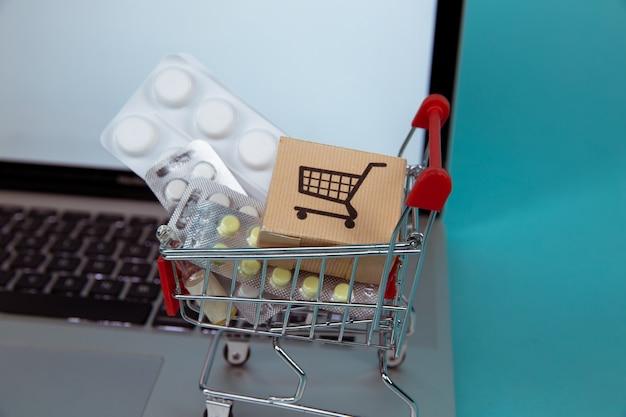 Mini koszyk pełen leków homeopatycznych na laptopie