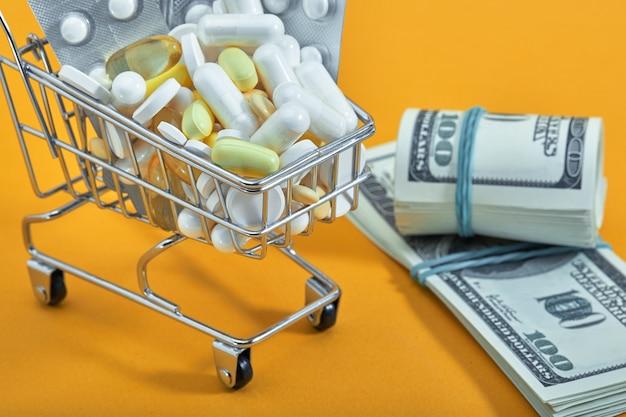 Mini koszyk, pigułki i kapsułki na żółtym tle. apteka internetowa. przemysł farmaceutyczny. epidemia, środki przeciwbólowe, koncepcja opieki zdrowotnej i leczenia. leżał płasko. miejsce na kopię.