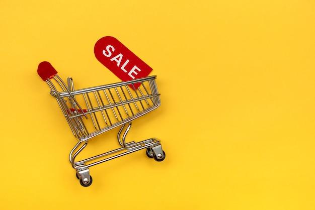Mini koszyk z czerwonym kuponem rabatowym. pojęcie sprzedaży i rabatów towarów.