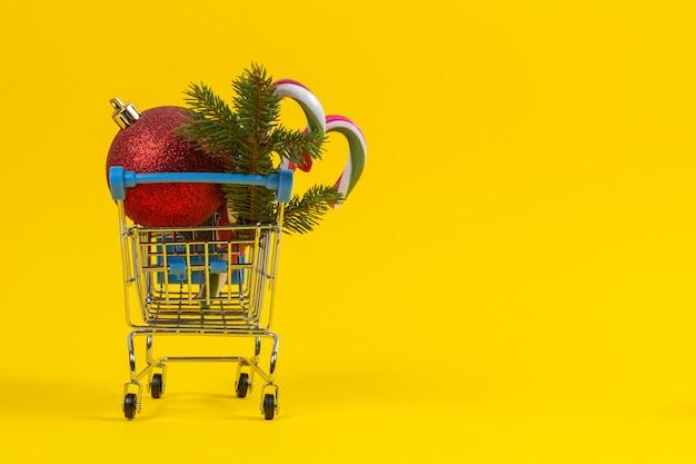 Mini koszyk ze świątecznymi dekoracjami, cukierkami na żółto