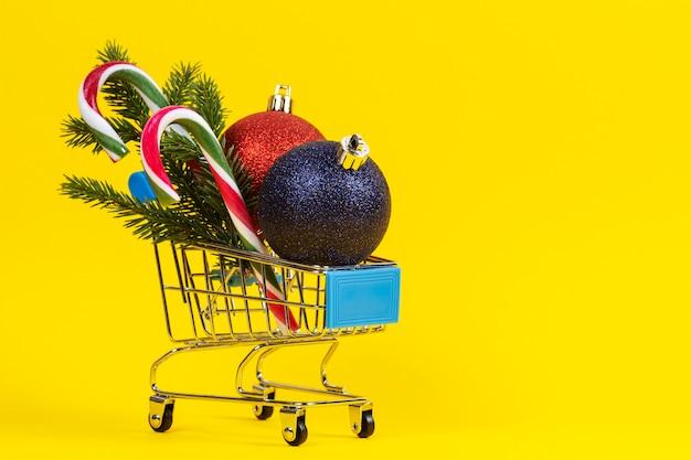 Mini koszyk ze świątecznymi dekoracjami i gałązką jodły na żółto