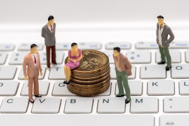 Mini ludzie na klawiaturze z monetami