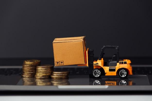 Mini model wózka widłowego z kartonami i monetami na zbliżeniu klawiatury. koncepcja logistyki i dostawy