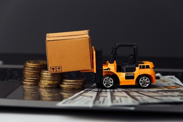 Mini model wózka widłowego z pudełkami i pieniędzmi na zbliżeniu klawiatury