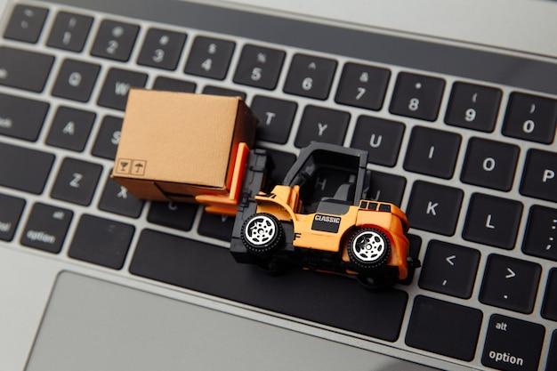 Mini model wózka widłowego z pudełkiem kartonowym na laptopie. koncepcja logistyki i dostawy. widok z góry