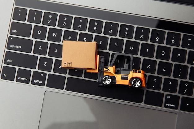 Mini model wózka widłowego z pudełkiem na laptopa. koncepcja logistyki i dostawy