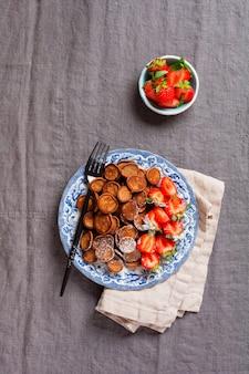 Mini naleśniki czekoladowe z truskawkami na śniadanie na szarym starym obrusie tekstylnym. modne domowe śniadanie z drobnymi naleśnikami. widok z góry