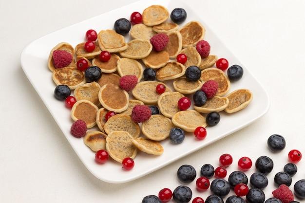 Mini naleśniki i jagody na talerzu. czerwone porzeczki, jagody