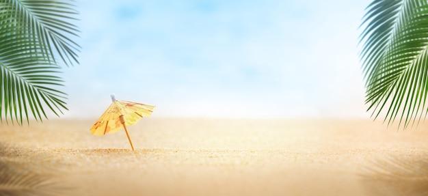 Mini parasol plażowy z liśćmi palmowymi, koncepcja lato na plaży