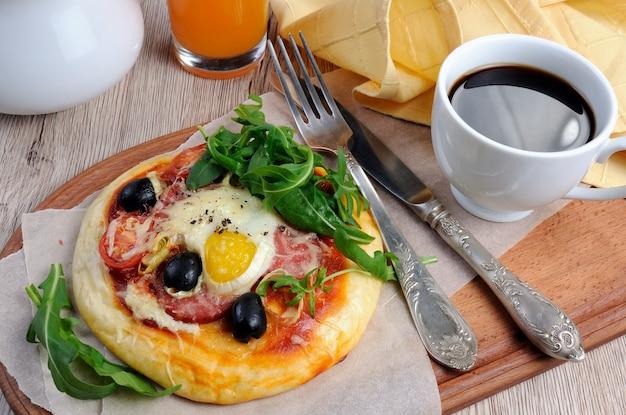 Mini pizza z kiełbasą i jajkiem i rukolą filiżanka kawy na śniadanie
