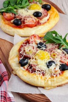 Mini pizza z kiełbasą i jajkiem i rukolą na śniadanie