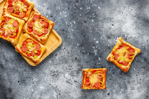 Mini pizze z ciasta francuskiego z kiełbasami.