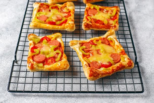 Mini pizze z ciasta francuskiego z kiełbaskami.