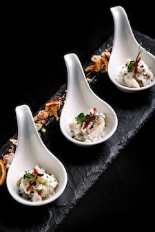 Mini porcje ceviche z okonia morskiego podawane w pięknych chińskich łyżkach na czarnym płaskowyżu. koncepcja żywności dla gastronomii.