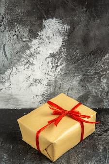Mini prezent z widokiem z przodu z czerwoną wstążką na ciemnej wolnej przestrzeni