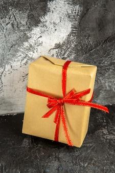 Mini prezent z widokiem z przodu z czerwoną wstążką na ciemnym