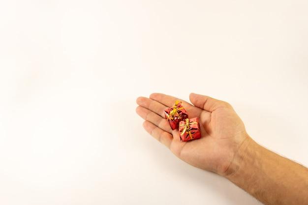 Mini prezenty w ręku na białym tle