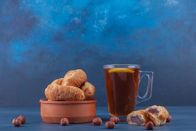 Mini rogaliki z ciasta francuskiego ze złotą skórką i filiżanką herbaty.