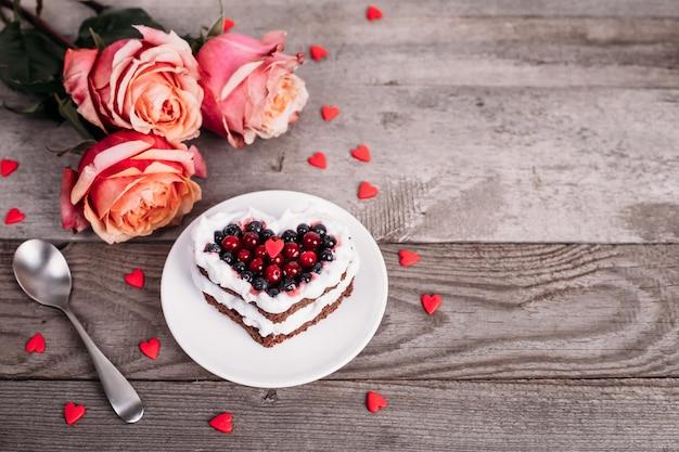 Mini romantyczne ciasto deserowe na walentynki z różami. słodkie ciasteczka z kremową polewą i czerwonym sercem do wystroju na drewnianym stole. makro, miejsca kopiowania.
