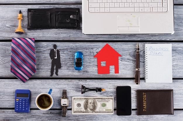 Mini samochód, papierowy dom i moja sylwetka w środku. rzeczy odnoszącego sukcesy biznesmena. przedmioty osobiste dookoła.