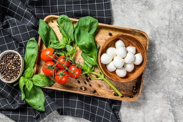 Mini ser mozzarella, liście bazylii i pomidory czereśniowe, gotowanie sałatki caprese. szare tło. widok z góry