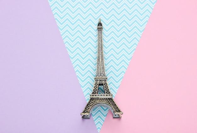 Mini statuetka wieży eiffla na pastelowym papierowym stole. widok z góry
