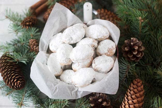 Mini stollen lub stollen candy w puszce na tle jodłowych gałęzi i szyszek.