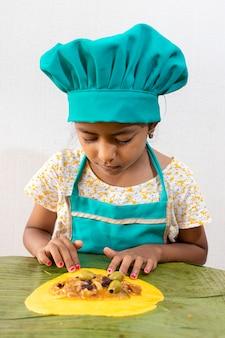 Mini szef kuchni przygotowuje typowe wenezuelskie hallaki