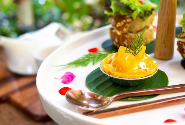 Mini tarta z mango podawana jest na białym talerzu i ozdobiona pięknymi kwiatami.