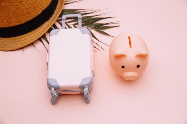 Mini walizka podróżna ze skarbonką na różowym stole