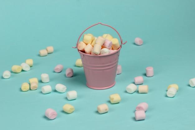 Mini wiaderko z dużą ilością pianek na pastelowym niebieskim tle. minimalizm. słodycze
