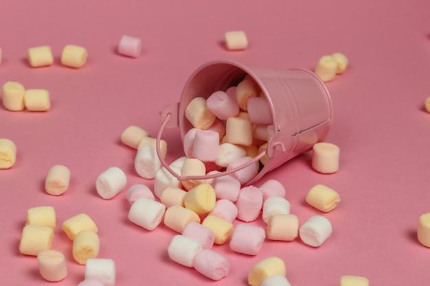 Mini wiaderko z dużą ilością pianek na różowym pastelowym tle. minimalizm. słodycze