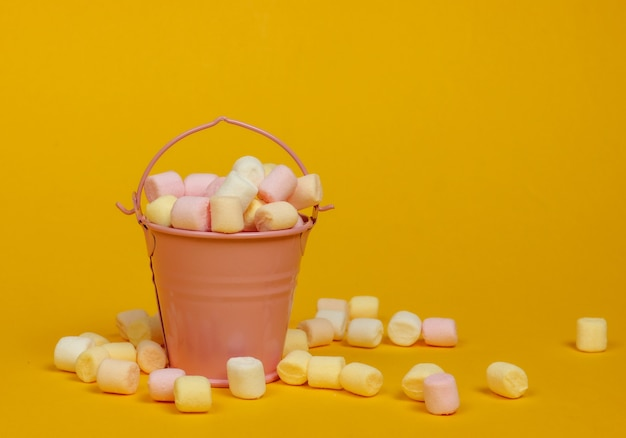 Mini wiaderko z dużą ilością pianek na żółtym tle. minimalizm. słodycze