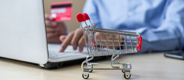 Mini wózek, azjatycki biznesmen posiadania karty kredytowej i za pomocą laptopa