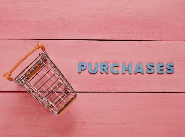 """Mini wózek na zakupy na czerwonym drewnianym tle z napisem """"zakupy"""""""