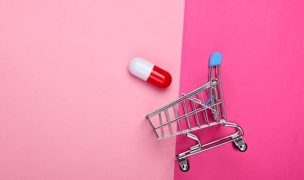 Mini wózek na zakupy, tabletka kapsułki na różowym tle. widok z góry