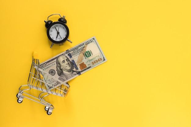 Mini wózek na zakupy z banknotami 100 dolarów w środku i mini budzikiem w kolorze żółtym