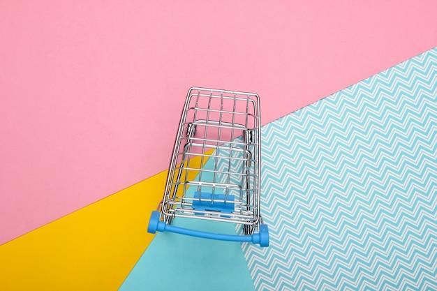 Mini wózek sklepowy na kolorowym pastelowym tle. widok z góry. koncepcja zakupy minimalizmu