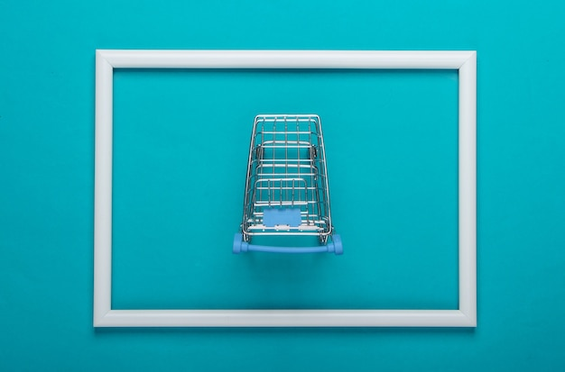 Mini wózek sklepowy na niebieskiej powierzchni z białą ramą