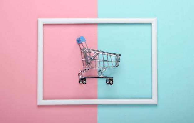 Mini wózek sklepowy na różowo-niebieskiej pastelowej powierzchni z białą ramą