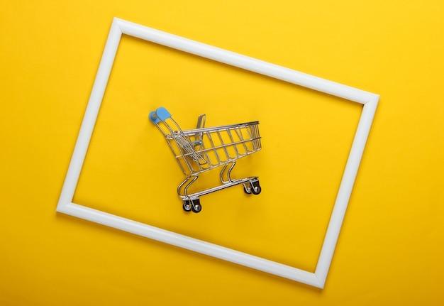 Mini wózek sklepowy na żółtej powierzchni z białą ramą