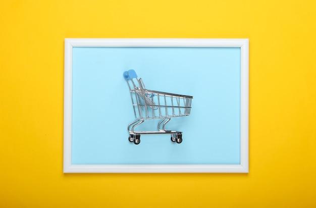 Mini wózek sklepowy na żółtej powierzchni z ramką na zdjęcia