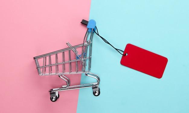 Mini wózek sklepowy z czerwoną metką na różowo-niebieskim pastelu.