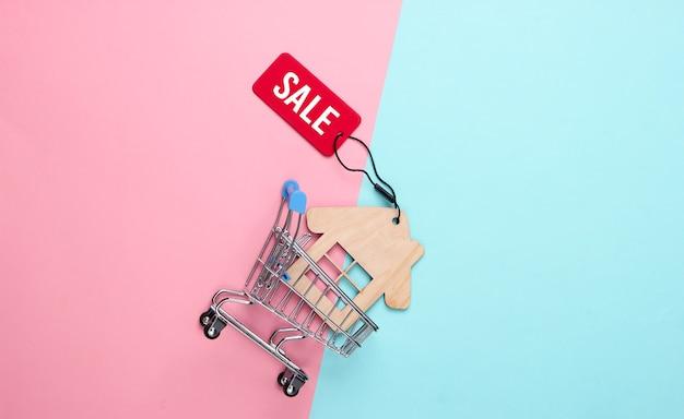 Mini wózek sklepowy z figurką domu i czerwoną etykietą sprzedaży na różowym niebieskim pastelowym kolorze.