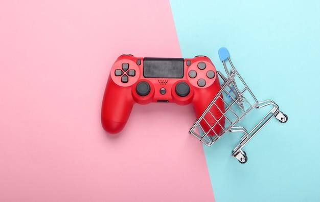 Mini wózek sklepowy z gamepadem na pastelowym różowo-niebieskim