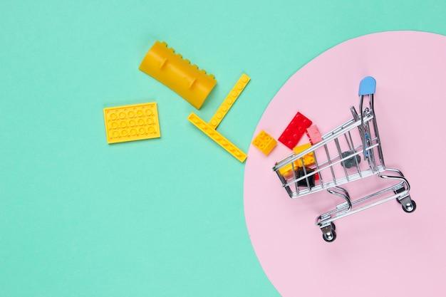 Mini wózek sklepowy z klockami zabawkowymi na niebiesko z różowym pastelowym kółkiem