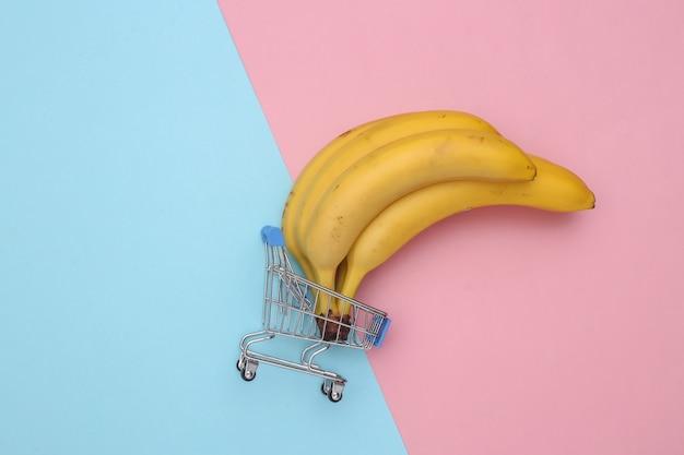 Mini wózek supermarketowy z dojrzałymi bananami na różowym niebieskim pastelowym tle.