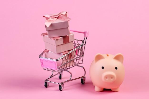 Mini wózek supermarketowy z pudełkami na prezenty i skarbonką na różowym pastelowym kolorze